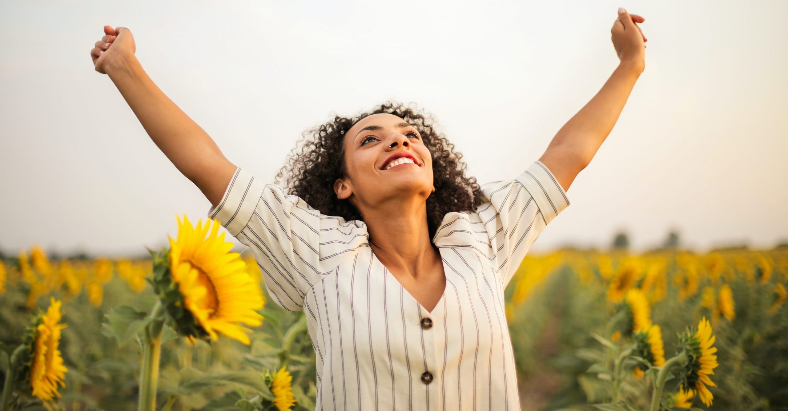 jeune-femme-souriante-dans-un-champs-de-tournesoles-les-bras-en-l-air