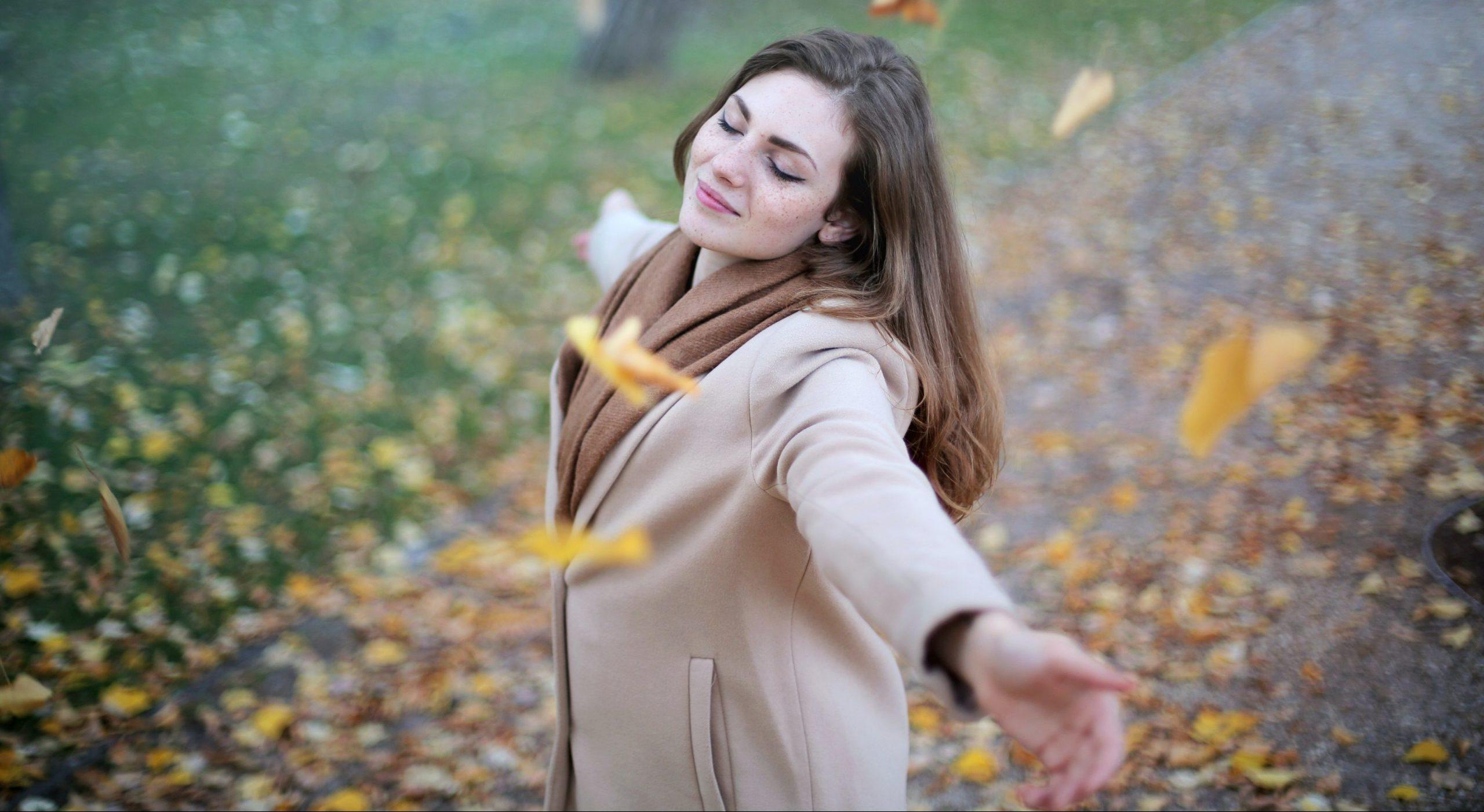 femme-détendue-avec-des-feuilles-qui-volent-autour-d-elle