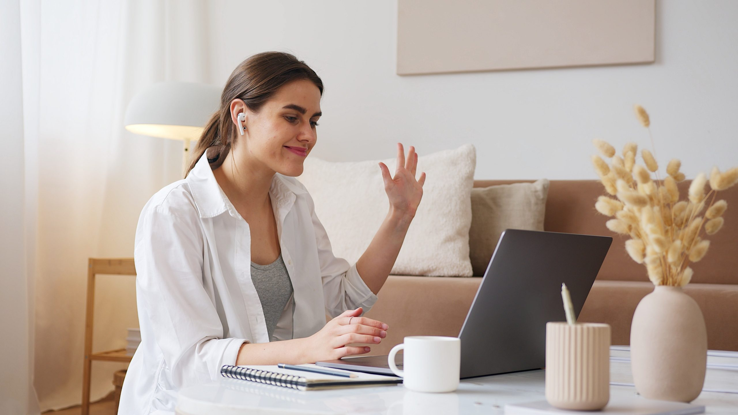 femme-souriante-devant-son-ordinateur-avec-un-carnet-de-notes
