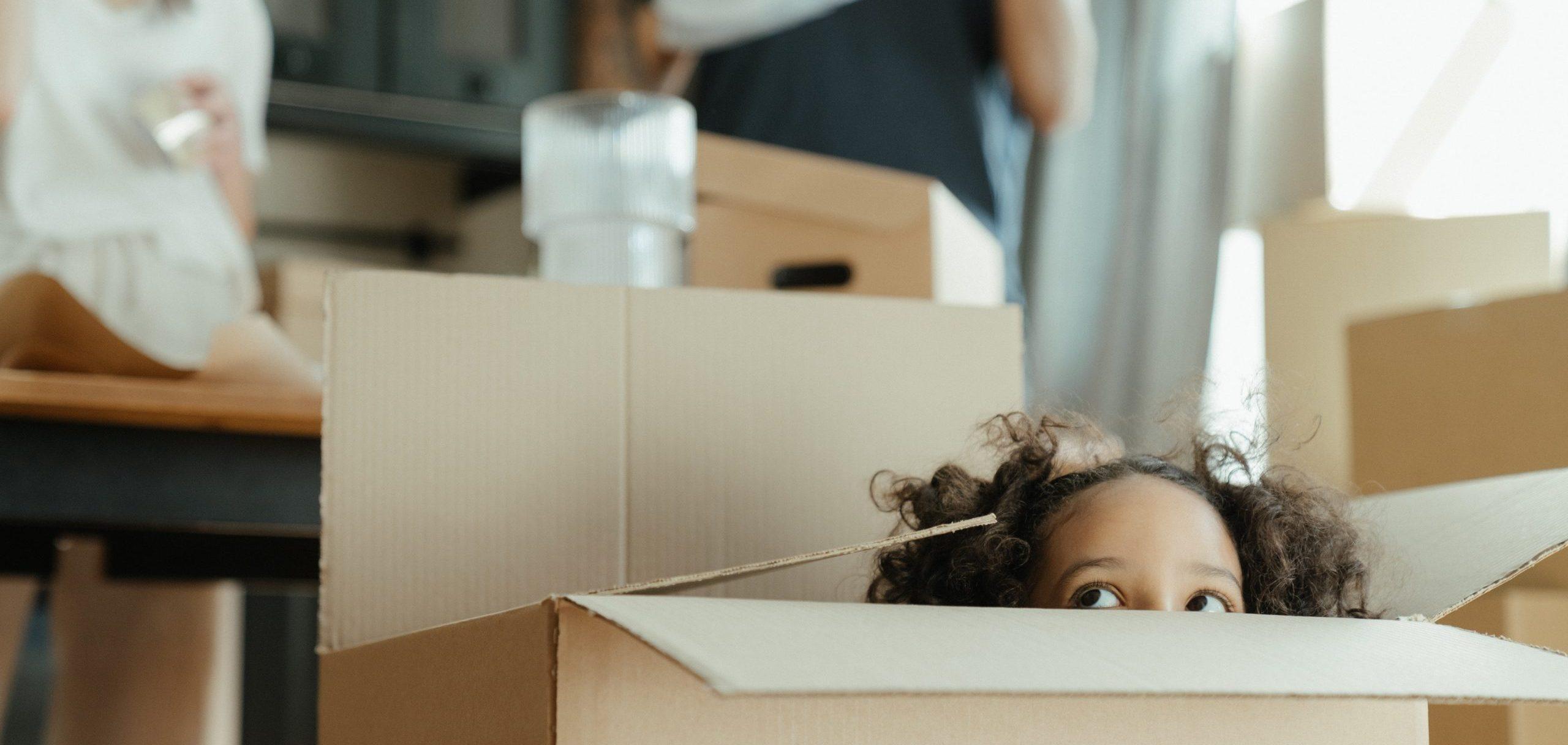 jeune-fille-qui-joue-avec-un-carton-d-emménagement