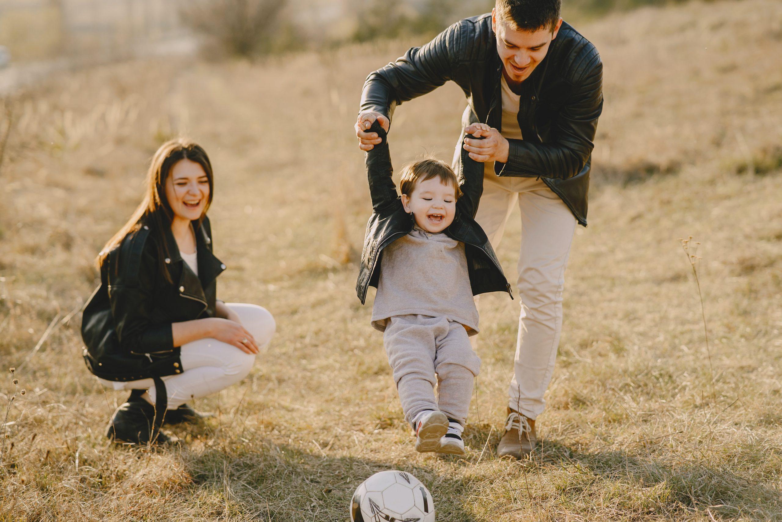 famille-heureuse-qui-joue-avec-un-ballon-en-extérieur