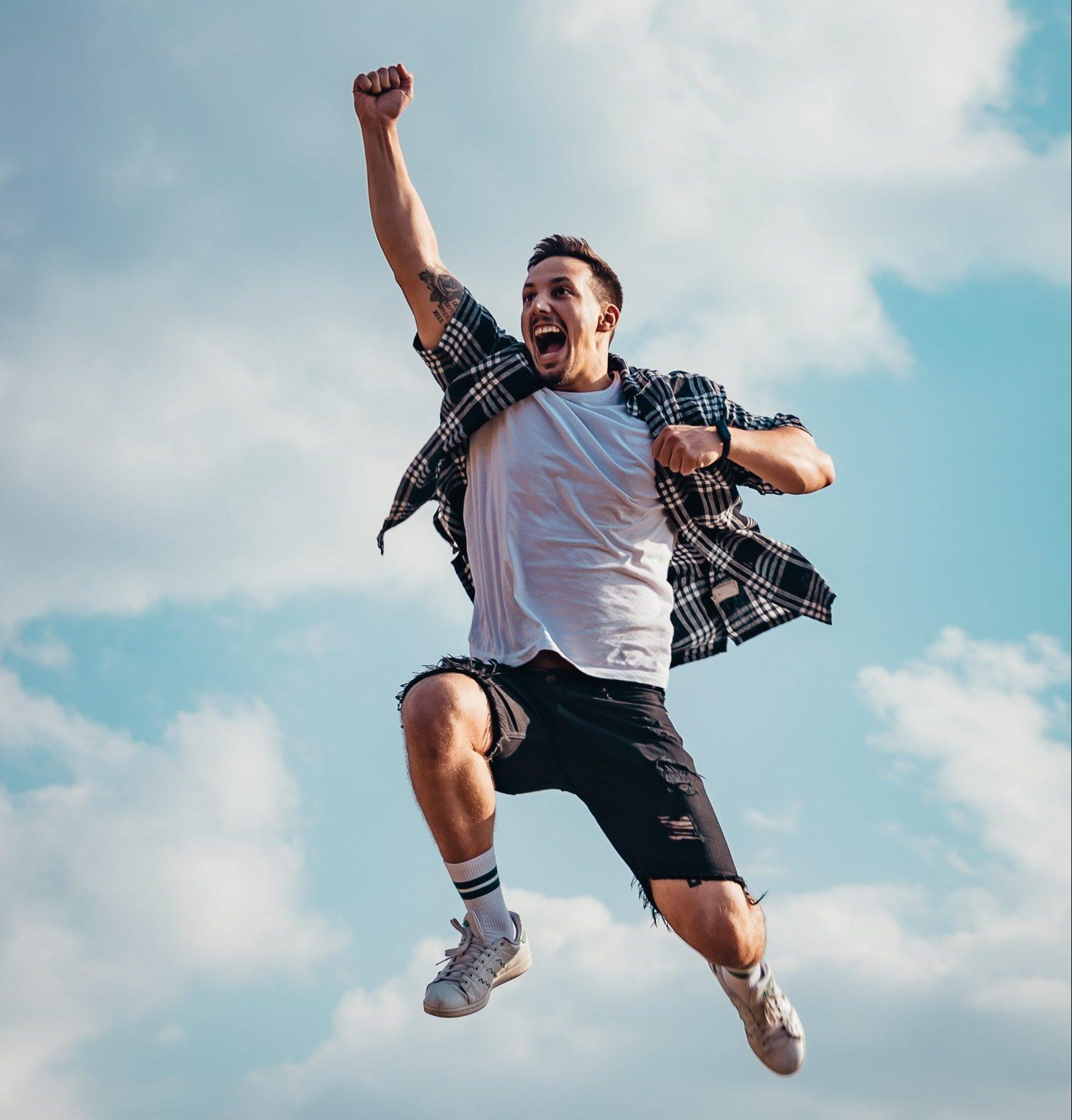 homme-heureux-saute-vers-le-ciel-le-poing-levé